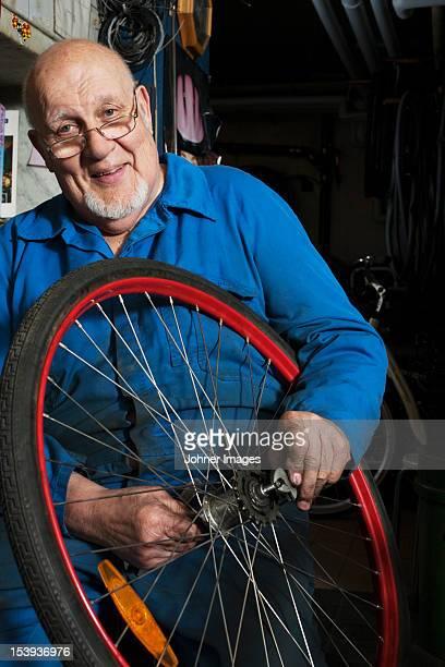 Senior man repairing tyre at repairing shop