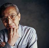 Senior man resting chin on hand, close-up, portrait