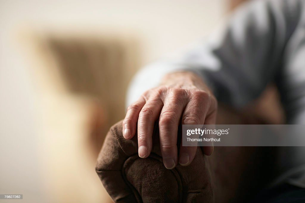 Senior man resting hand on side of armchair, close-up of hand