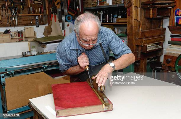 Senior man restoring book in traditional bookbinding workshop