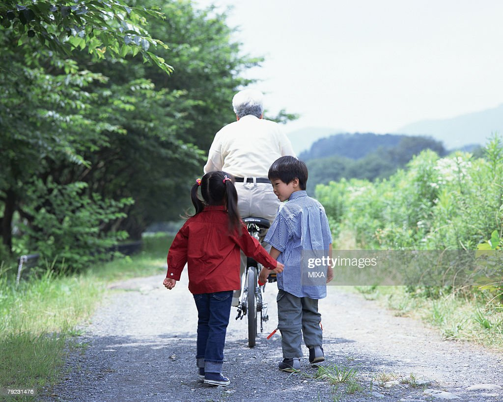 A senior man riding a bicycle with grand children walking after : Stock Photo