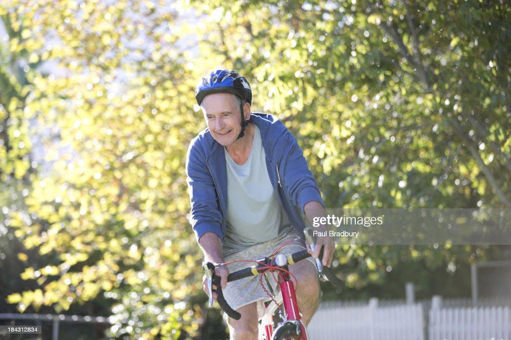 Senior man riding bicycle in park : Stock Photo