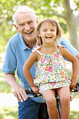 Senior man riding bike with granddaughter laughing