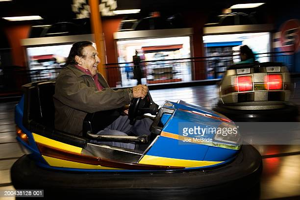 Senior man riding bumper car at amusement park