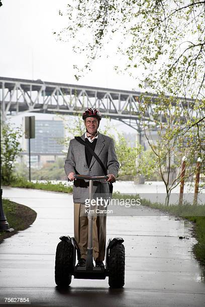 Senior man riding segway by river, portrait
