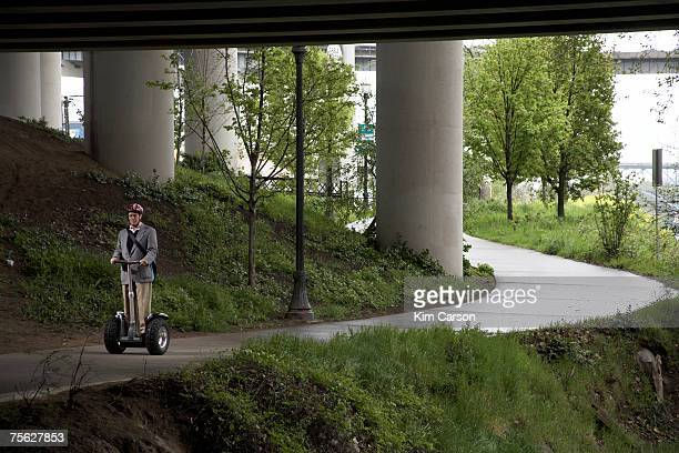 Senior man riding segway under underpass