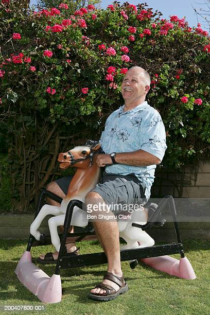 Senior man riding toy rocking horse, side view
