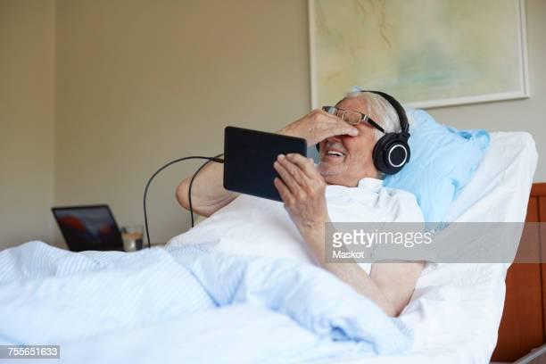 Senior man rubbing eyes while using digital tablet on bed in hospital ward