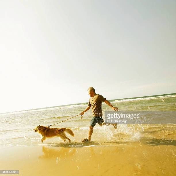 Senior Man Running At Beach With His Dog