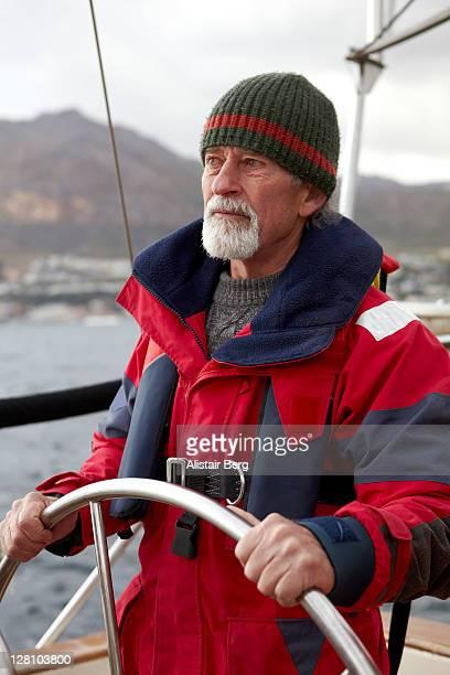 Senior man sailing a boat