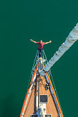 Senior man seen sailing from above with arms outstretched, San Diego, California, USA