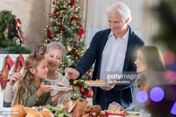 Senior man serveert taart aan kleindochter kerstdiner