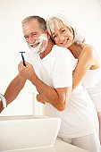 Senior Man Shaving In Bathroom Mirror With Wife Watching