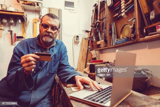 Senior man shopping online with credit card