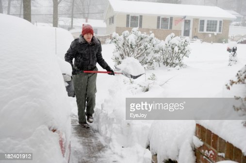 Senior Man Shoveling Snow in Suburbia During Storm