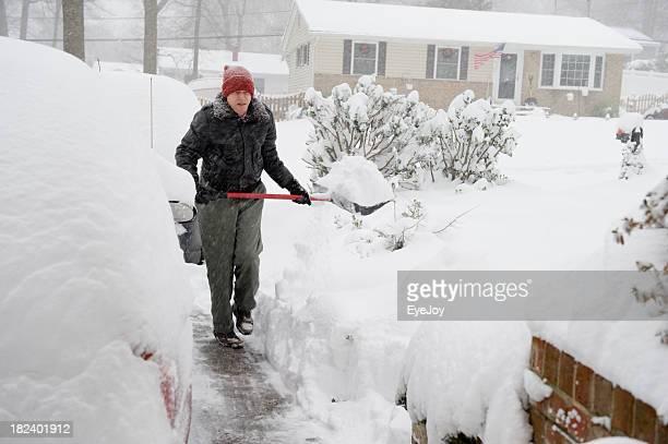 Senior Man Shoveling Snow in Suburbia During Storm