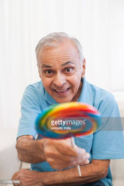 Senior man showing a lollipop and smiling
