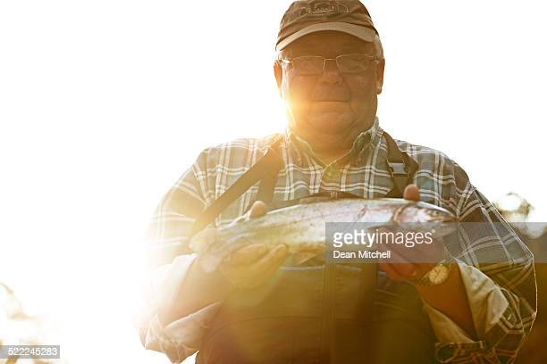 Senior man showing freshly caught fish
