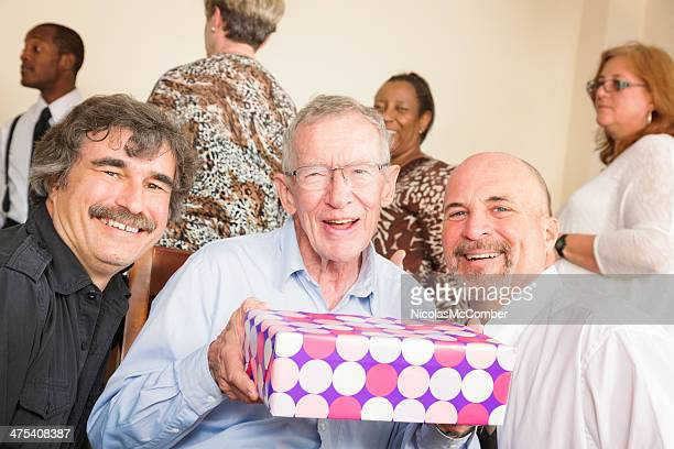 Senior man shows off birthday gift at family party