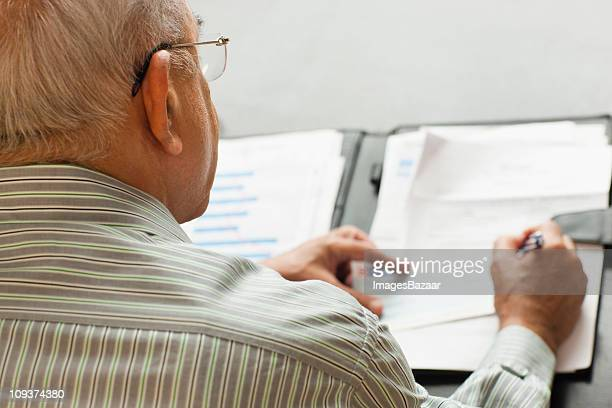 Senior man signing document on table