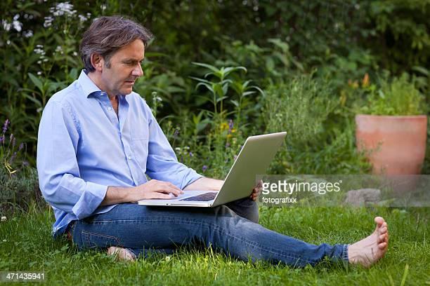 senior man sits barefoot on grass while working at laptop