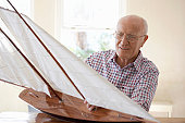 Senior Man Sitting at a Table and Examining a Model Yacht