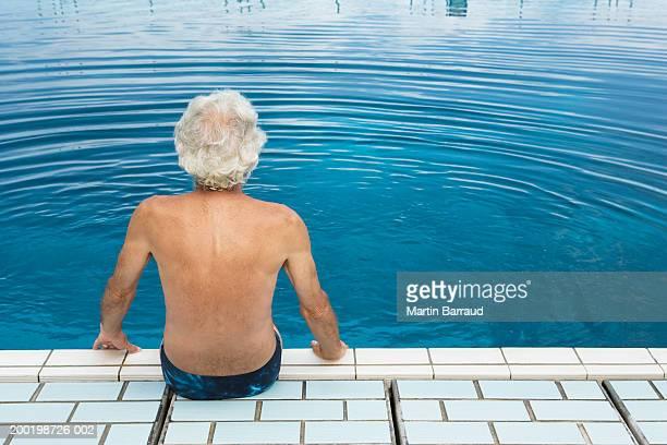 Senior man sitting at edge of swimming pool, rear view