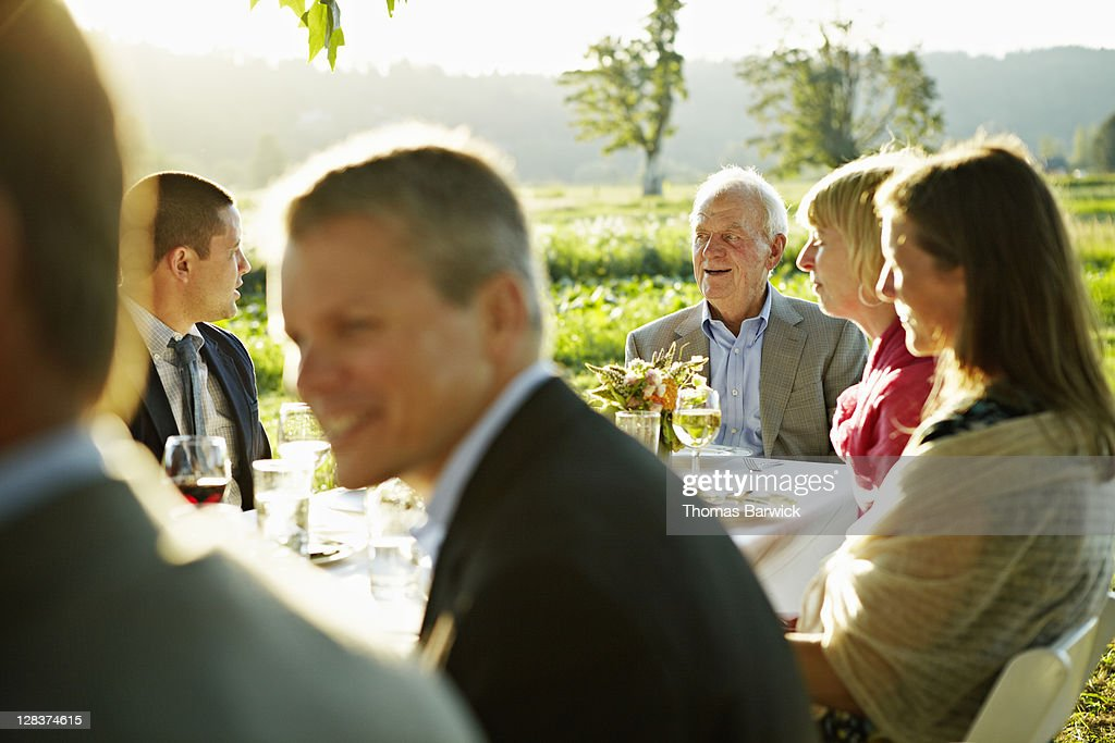 Senior man sitting at head of table outside : Stock Photo