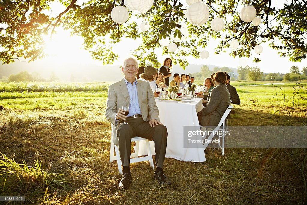 Senior man sitting at head of table outside