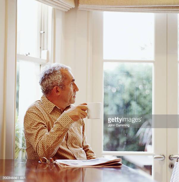 Senior man sitting at table holding mug, looking out window