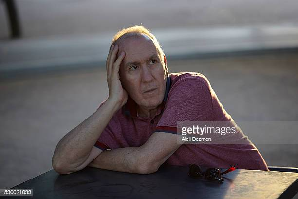 Senior man sitting at table, resting on elbow