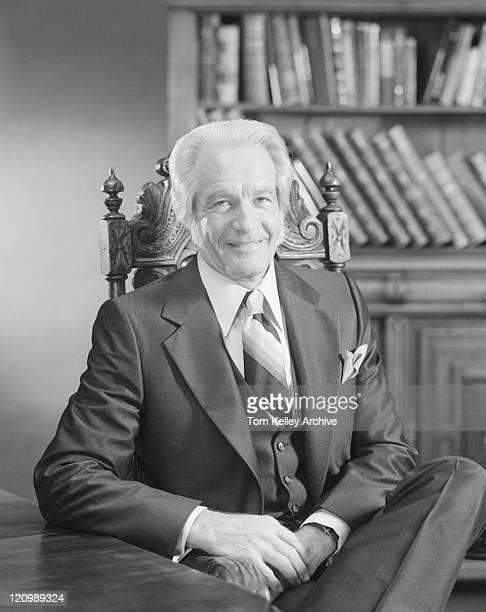 Senior man sitting at table, smiling, portrait