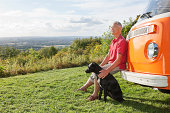 Senior man sitting by camper van with dog