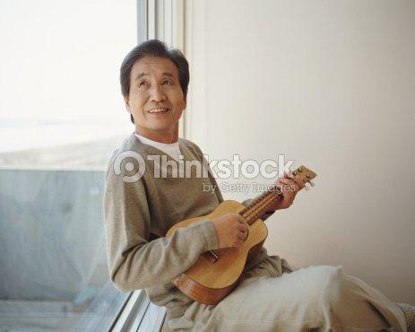 Senior homme assis par la fen tre regarder jouer ukul l for Assis a la fenetre