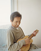 Senior man sitting by window playing ukelele