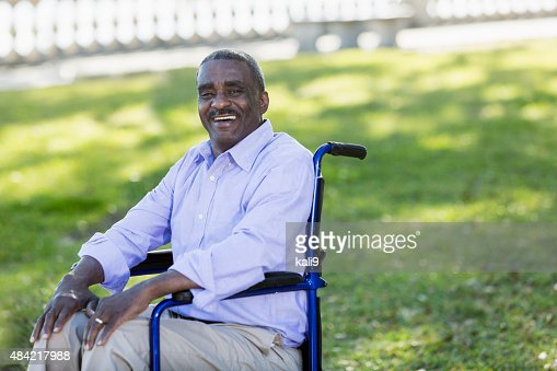 Senior man sitting in a wheelchair at the park