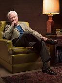 Senior man sitting in armchair, portrait