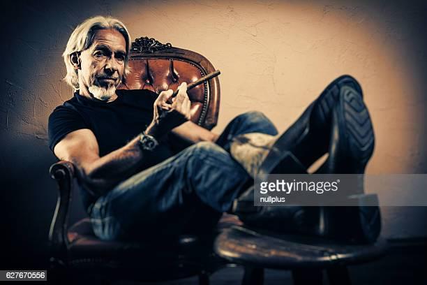 Senior man sitting in armchair, studio portrait