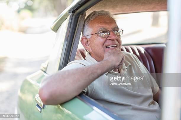 Senior man sitting in back seat of car, smiling