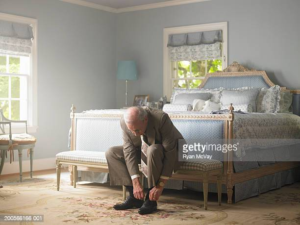 Senior man sitting in bedroom tying shoe laces