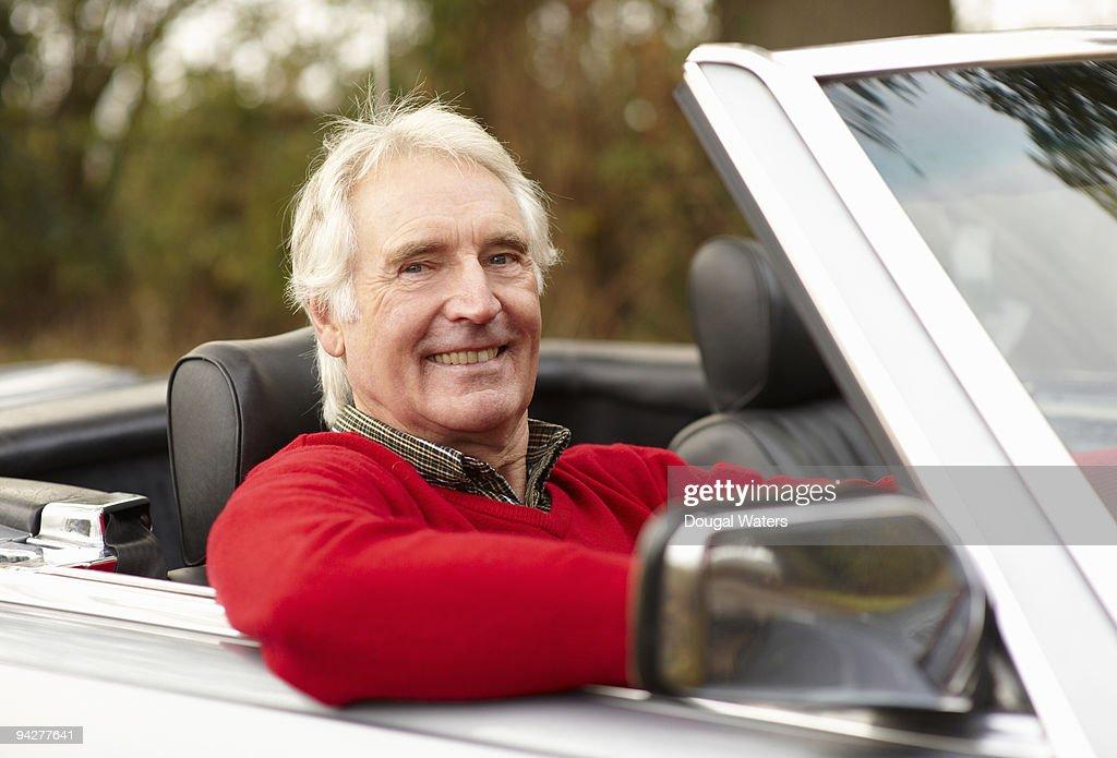 Senior man sitting in classic car. : Stock Photo