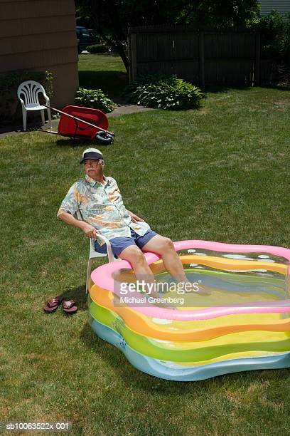 Senior man sitting in garden with feet in inflatable pool