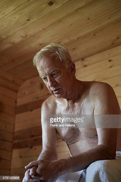 Senior man sitting in sauna with head down