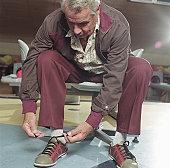 Senior man sitting inside bowling alley, tying shoes