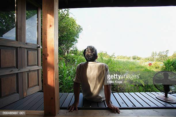 Senior man sitting, looking outdoors, rear view