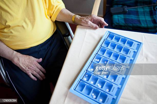 A senior man sitting next to a weekly pill organizer, focus on object