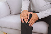 Senior man sitting on a sofa in the living room at home and touching his knee by the pain