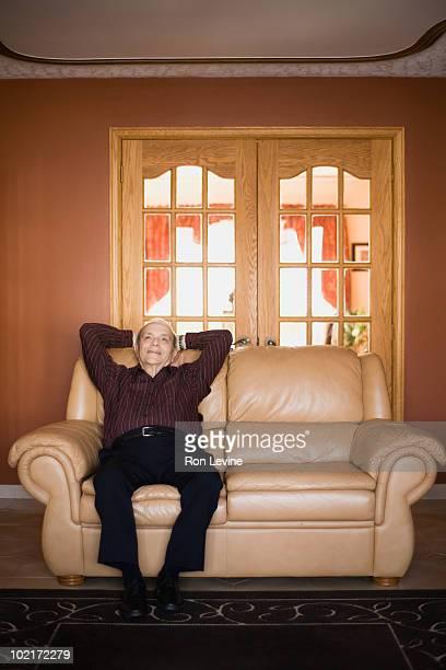 Senior man sitting on a sofa, relaxing