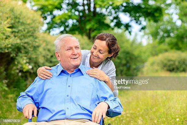 Älterer Mann sitzt auf einem Rollstuhl mit Der Fürsorgliche