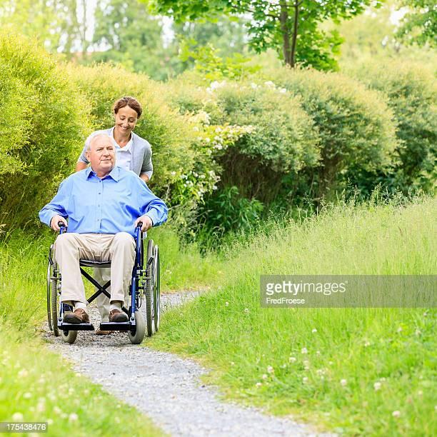 Senior man sitting on a wheelchair with caregiver